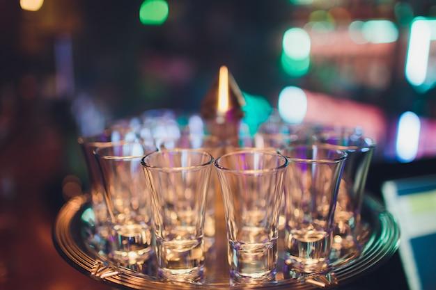 Lege geschotene glazen op bar tegen selectieve nadruk.