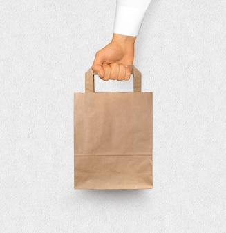 Lege geweven papieren zak mock-up houden in de hand geïsoleerd in de buurt van witte muur.