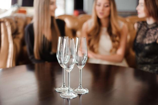 Lege glazen champagne op de achtergrond van de meisjes