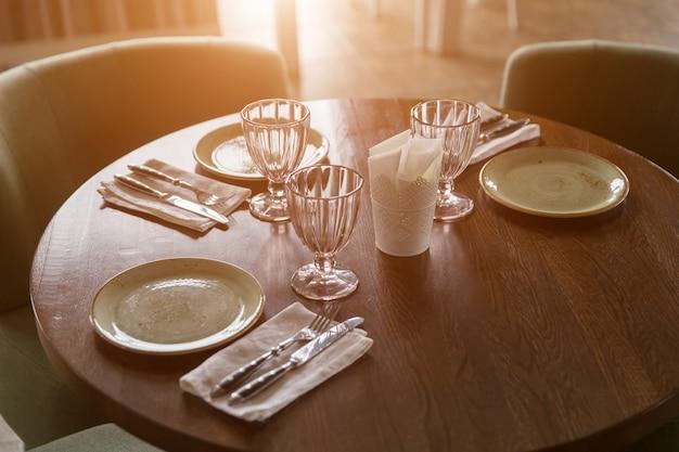 Lege glazen en borden in restaurant met zonlicht