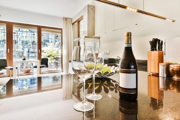 Lege glazen en fles wijn op de toonbank van dure keuken met panoramische ramen bij daglicht