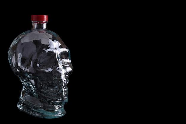 Lege glazen fles in de vorm van een schedel op een zwarte achtergrond met kopie ruimte