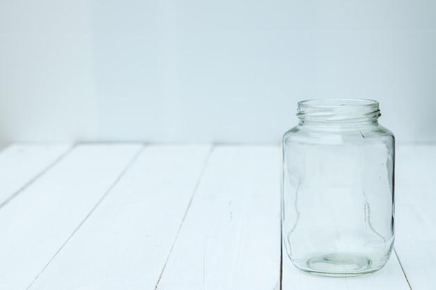 Lege glazen fles op de houten witte tafel.