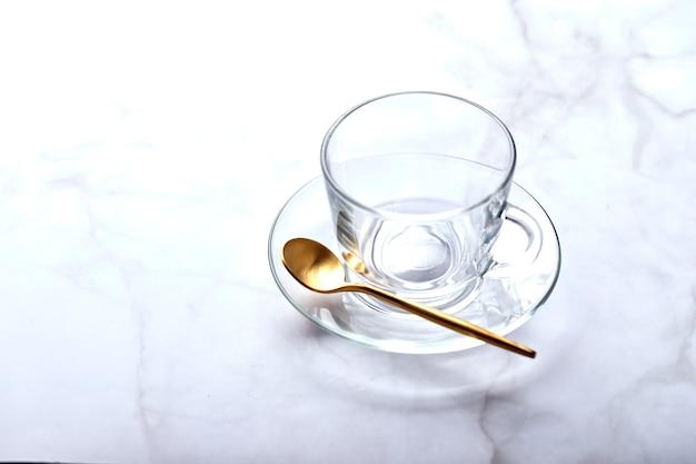 Lege glazen kop op schotel met gouden lepel op lichte marmeren tafel