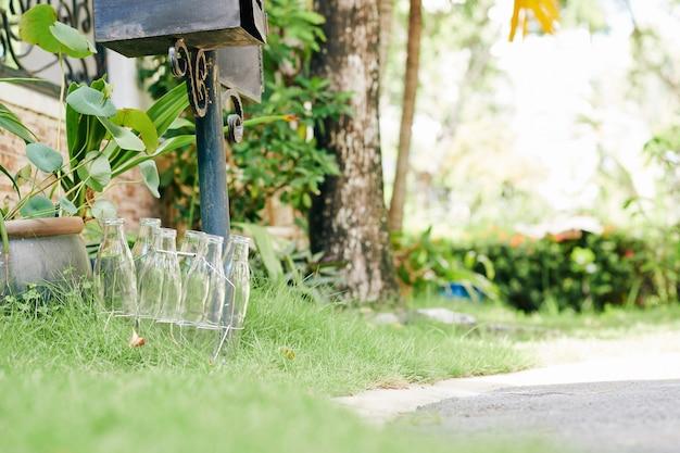 Lege glazen melkflessen op gazon naast brievenbus