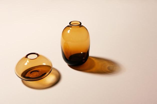Lege glazen vazen op beige achtergrond met harde lange schaduwen met kopieerruimte, horizontaal