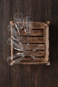 Lege glazen voor champagne in een houten kist voor de nieuwjaarstafel
