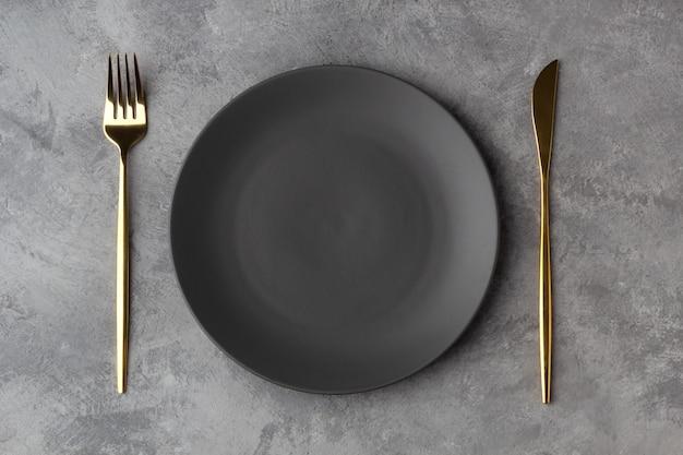 Lege grijze plaat met een gouden mes en vork op een grijze betonnen achtergrond