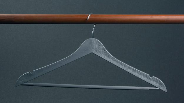 Lege grijze plastic kleerhanger die op dark hangt