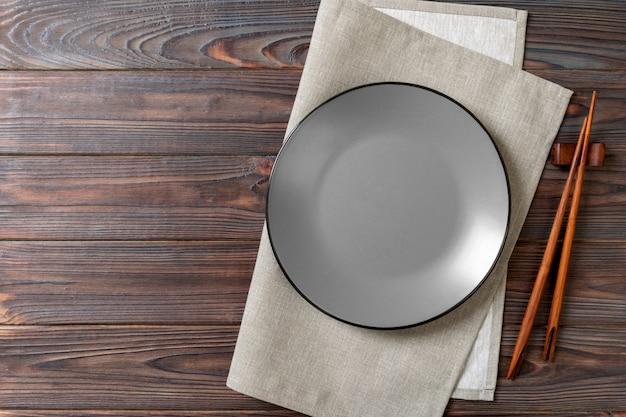 Lege grijze ronde plaat met eetstokjes voor sushi op hout