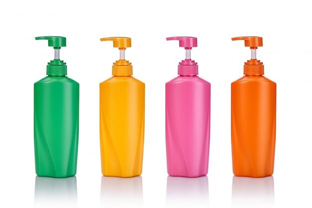 Lege groene, gele, roze en oranje plastic pompfles die wordt gebruikt voor shampoo of zeep.