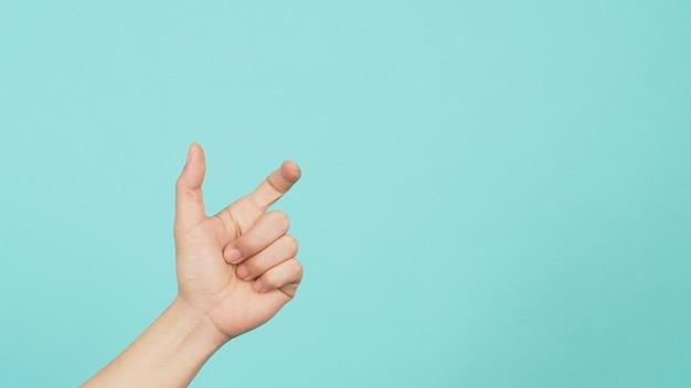 Lege hand die niets vasthoudt of vangt op groene en blauwe of muntachtergrond.