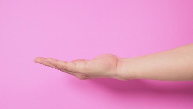 Lege hand op roze achtergrond.