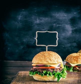Lege houten aanwijzer zit vast in een grote hamburger met een gehaktbal