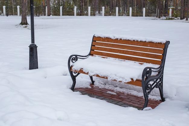 Lege houten bank bedekt met sneeuw in winter park