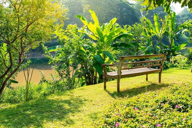 Lege houten bank in de tuin met uitzicht op de rivier