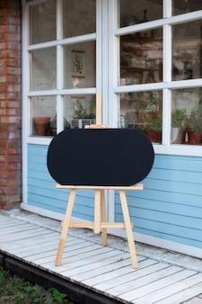 Lege houten ezel op straat. bord op straat. zwarte raad met houten frame dat zich in tuin bevindt.