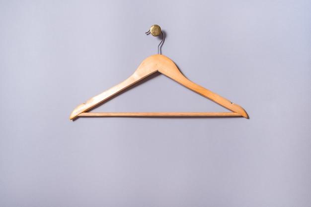 Lege houten gelakte kleerhanger hangen aan grijze muur, op messing cnob