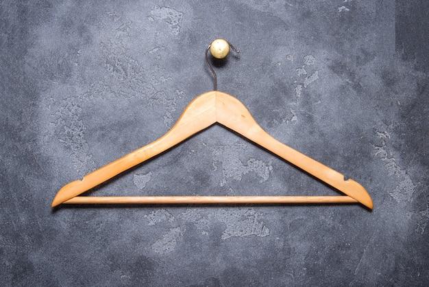 Lege houten gelakte kleerhanger hangen aan grijze stenen muur, op messing cnob
