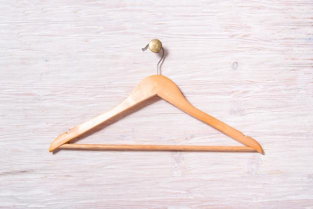 Lege houten gelakte kleerhanger hangen aan witte houten muur, op messing cnob