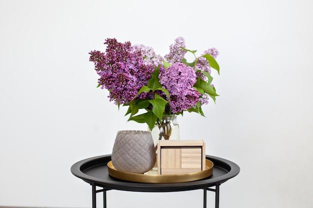 Lege houten kalender naast boeket van lila bloemen in vaas en kandelaar op een vintage salontafel.