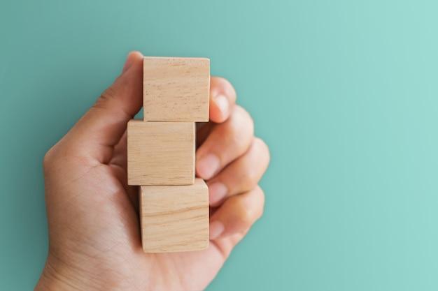 Lege houten kubus waarop u tekst of pictogram op de achtergrond in de hand kunt zetten
