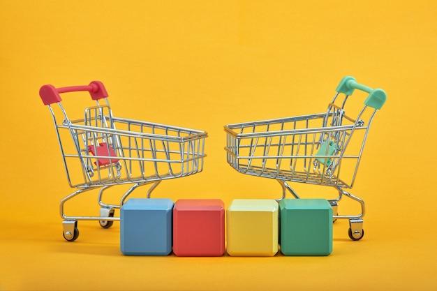 Lege houten kubussen mockup stijl, kopie ruimte met winkelwagentjes op gele achtergrond