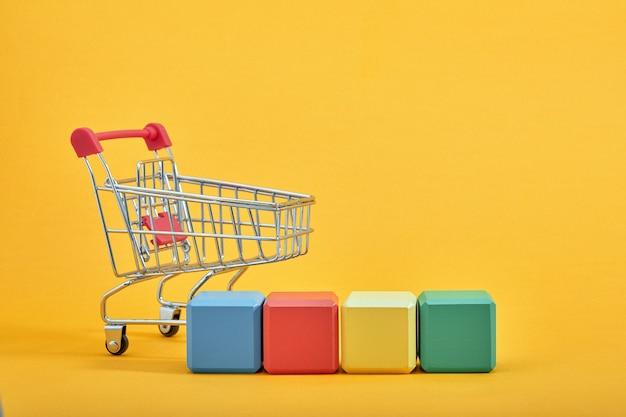 Lege houten kubussen mockup-stijl, kopie ruimte met winkelwagentjes op gele achtergrond