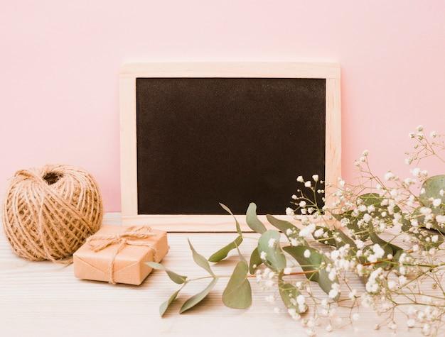Lege houten lei met spoel; geschenkdoos en baby's-adem bloemen op houten bureau tegen roze achtergrond