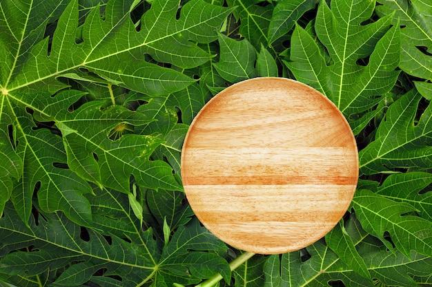 Lege houten plaat op de achtergrond van papajabladeren.