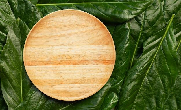Lege houten plaat op de bladerenachtergrond van noni of morinda citrifolia. bovenaanzicht
