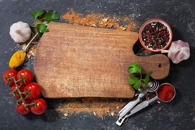 Lege houten plank met diverse producten voor het koken op donkere achtergrond, bovenaanzicht