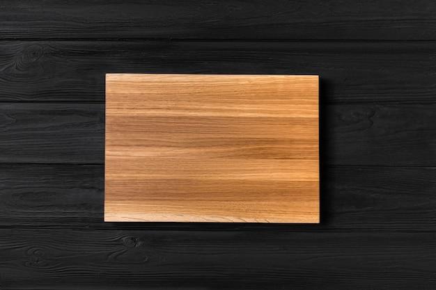 Lege houten plank op een zwarte houten achtergrond