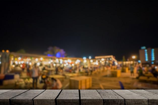 Lege houten plankenvertoning met de achtergrond van de nachtmarkt
