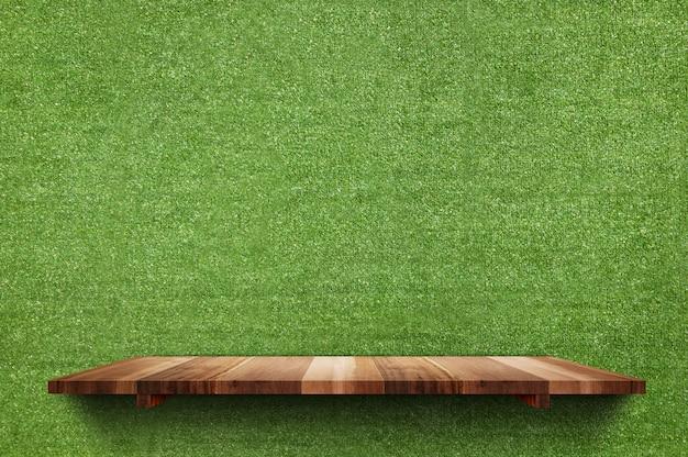 Lege houten raadsplank bij de nep groene achtergrond van de grasmuur