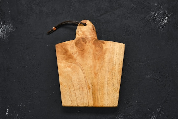 Lege houten snijplank op zwarte sjofele achtergrond