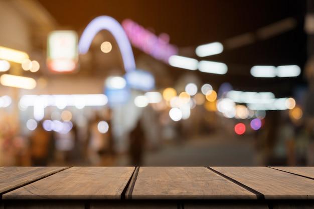 Lege houten tafel aan de voorkant wazig kleurrijke nacht straat achtergrond
