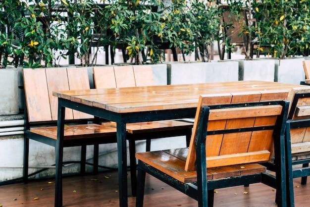 Lege houten tafel en stoel in openluchtrestaurant
