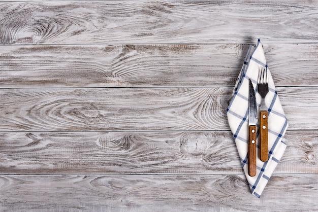 Lege houten tafel en vork en mes op servet.