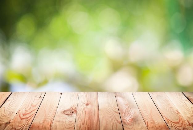 Lege houten tafel met gebladerte bokeh oppervlak. Premium Foto