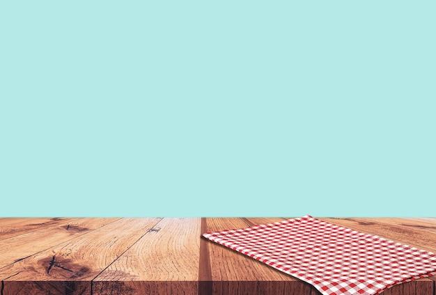 Lege houten tafel met rood geruit tafelkleed op blauw