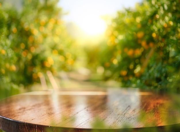 Lege houten tafel met vrije ruimte over sinaasappelbomen, oranje veld achtergrond. voor montage van productweergave: