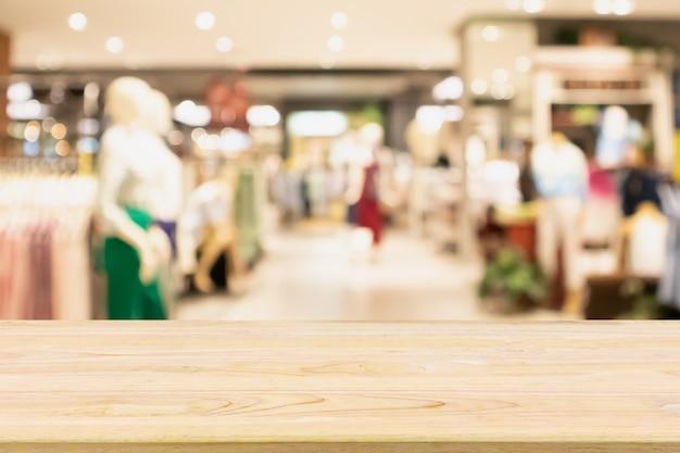 Lege houten tafel met vrouw modieuze boutique kleding winkel etalage in winkelcentrum