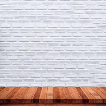 Lege houten tafel met witte bakstenen muur.