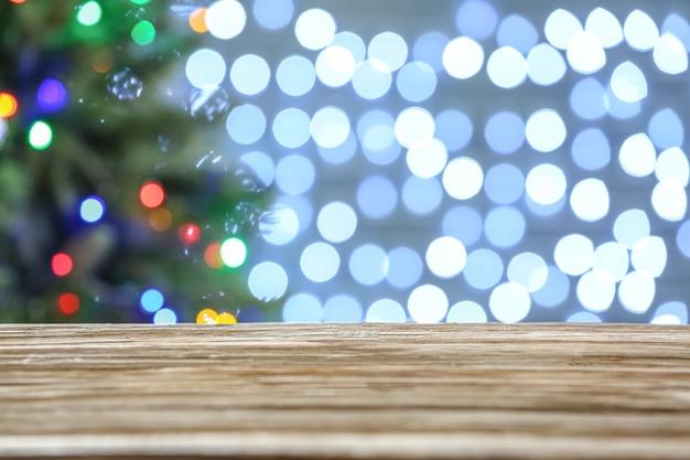 Lege houten tafel tegen wazig kerstverlichting