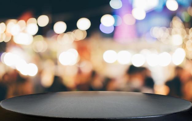Lege houten tafel voor abstracte wazig feestelijke lichte achtergrond met lichte vlekken en bokeh