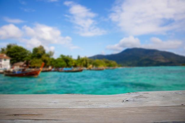 Lege houten tafel voor huidig product met zachte onscherpte natuurlijke zee met bergachtergrond