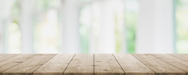 Lege houten tafelblad en vervagen glazen venster interieur restaurant