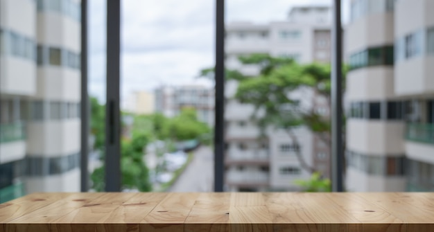 Lege houten tafelblad en vervagen glazen venster muur banner achtergrond bouwen