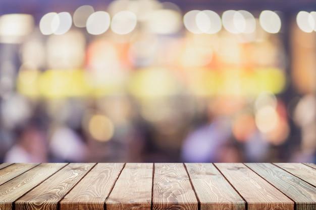 Lege houten tafelblad en wazig bokeh cafe en koffie winkel interieur achtergrond.